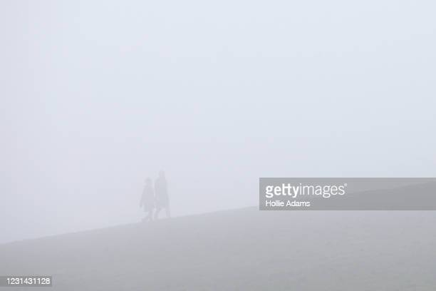 People walking in the fog at Parliament Hill on February 28, 2021 in London, England. February concluded with springlike temperatures around the UK...