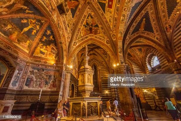 People walking in the interior of the Baptistery next to the Baptismal Font at the city of Siena in Tuscany, Italy.