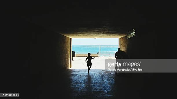 people walking in tunnel - cascais stock photos and pictures
