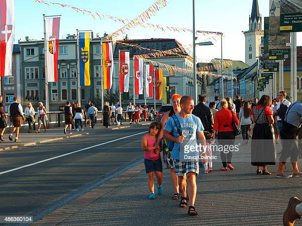 people walking near villacher kirchtag festival in austria. - carinthia stock pictures, royalty-free photos & images