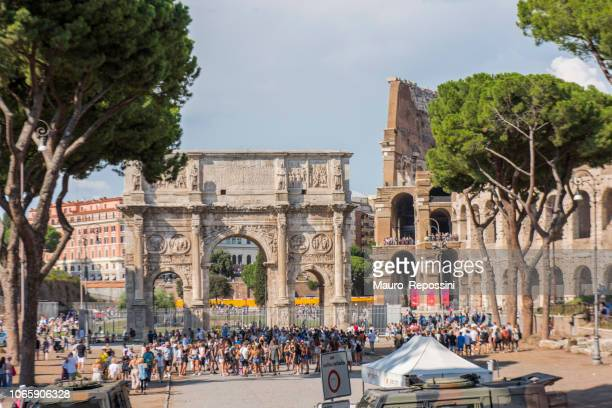 People walking next to the Arch of Constantine and the Coliseum at Rome, Italy.