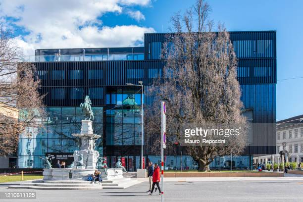 people walking next to the haus der musik (house of music) at innsbruck city, austria. - musik stock pictures, royalty-free photos & images