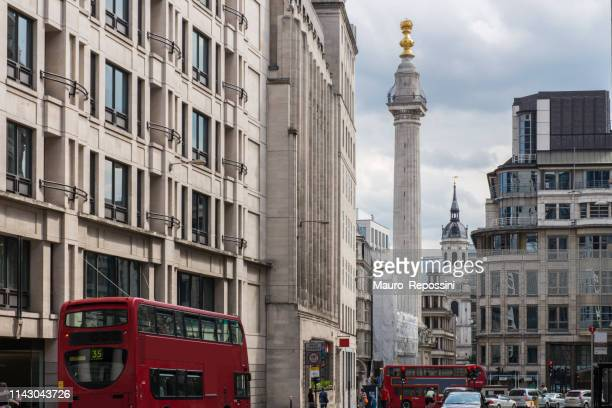 """people walking next to the monument to the great fire of london, known as """"the monument"""", at the city of london, england, uk. - great fire of london stock photos and pictures"""