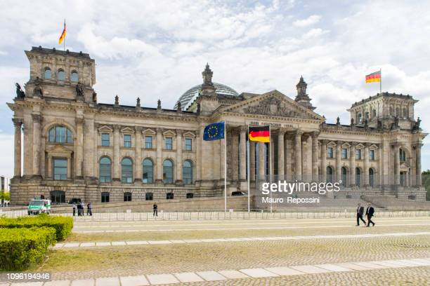 people walking next to the reichstag building at berlin city, germany. - bundestag stock pictures, royalty-free photos & images