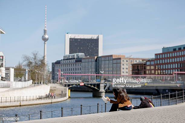 People walking next to the river Spree with the Berlin TVtower called 'Alex' in the background on April 20 2014 in Berlin Germany Berlin is the...