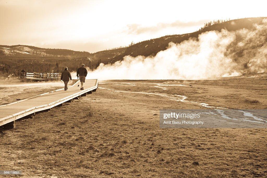 People walking on a boardwalk towards a geyser : Stock Photo
