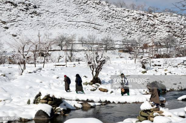 People walking on a footbridge over a stream in Daksum about 97 kilometers south of Srinagar city the summer capital of Indiancontrolled Kashmir Feb...