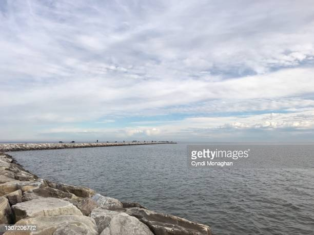 people walking on a rocky jetty leading out to the chesapeake bay, north point state park - maryland us state stock pictures, royalty-free photos & images