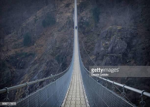 people walking on a suspension footbridge - hängebrücke stock-fotos und bilder