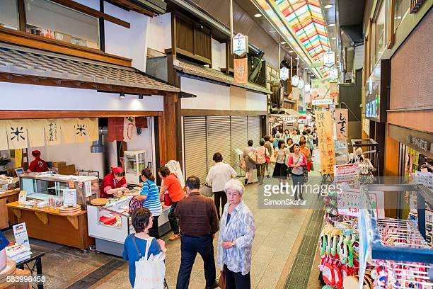 people walking on alley at nishiki market - nishiki market stock photos and pictures
