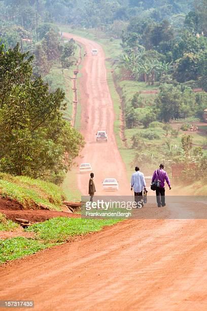 People walking on an african dusty dirt road.