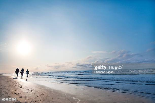 people walking on beach at sunrise - hilton head stock pictures, royalty-free photos & images