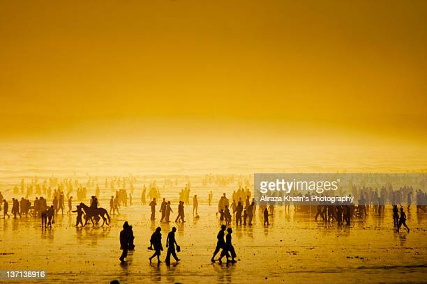 People walking on beach at sunset