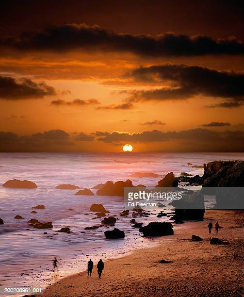 people walking on beach at sunset - zuma beach stock photos and pictures