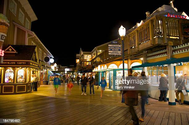people walking on boardwalk near popular shops - fishermans wharf stock pictures, royalty-free photos & images