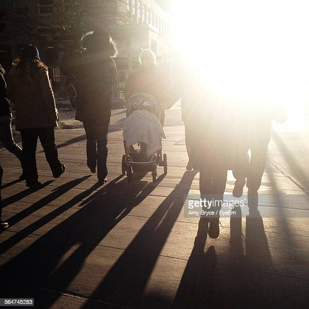 people walking on boardwalk - medium group of people stock pictures, royalty-free photos & images