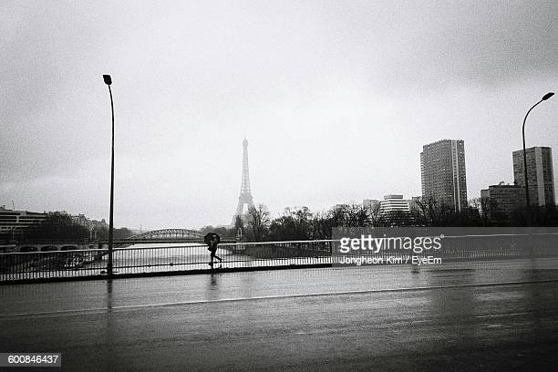 People Walking On Bridge Over River By Eiffel Tower Against Sky During Monsoon