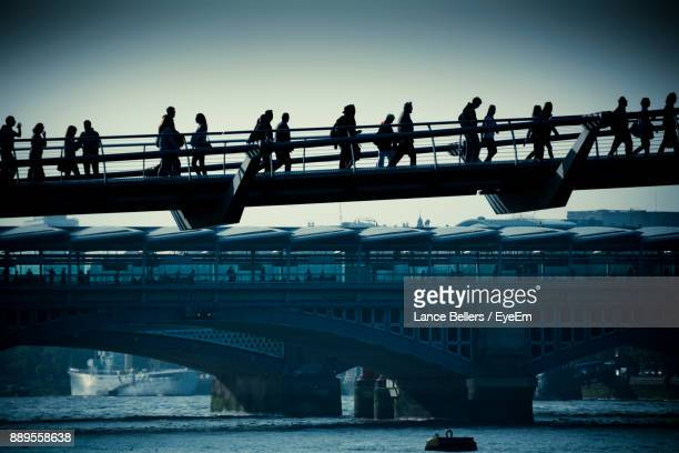People Walking On Bridge Over River