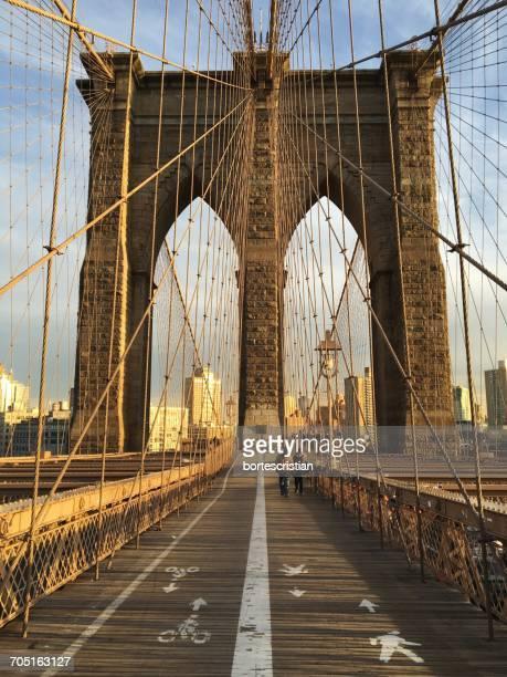 people walking on brooklyn bridge in city - bortes foto e immagini stock