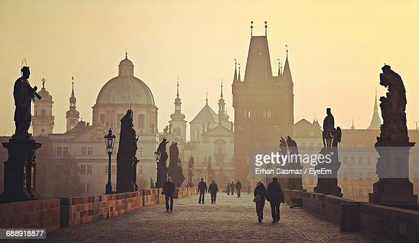 people walking on charles bridge by buildings against sky - charles bridge stock photos and pictures