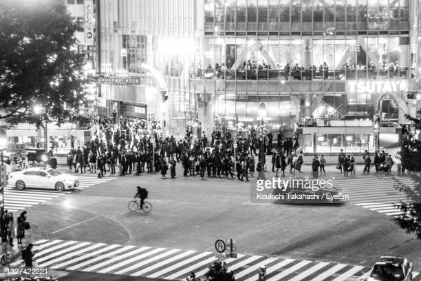 people walking on city street at night in shibuya crossing tokyo japan - monochrome - koukichi stock pictures, royalty-free photos & images