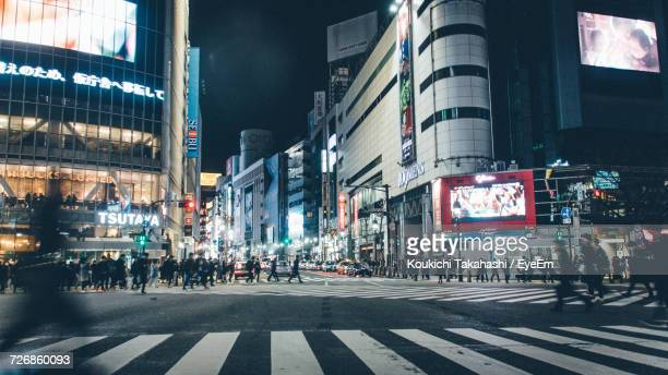 people walking on city street at night - crossing stock pictures, royalty-free photos & images