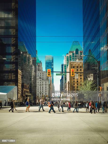 people walking on city street - vancouver canada stock photos and pictures