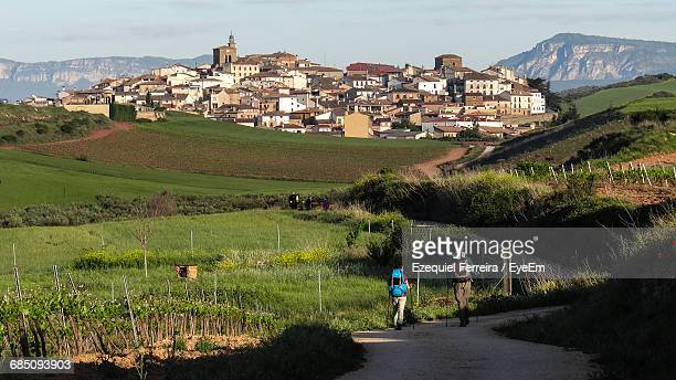 people walking on country road in town - camino de santiago stock pictures, royalty-free photos & images