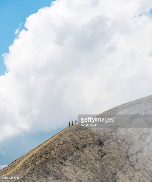 people walking on crater rim, smoking mount bromo, bromo tengger semeru national park, java, indonesia - bromo crater stock pictures, royalty-free photos & images