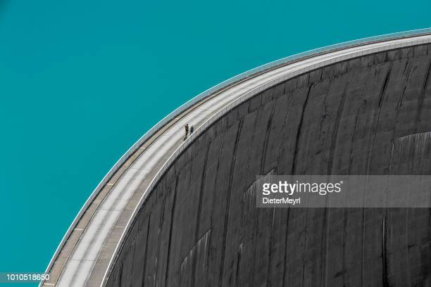 people walking on edge of stausee mooserboden dam, kaprun, austria - hydroelectric power stock pictures, royalty-free photos & images
