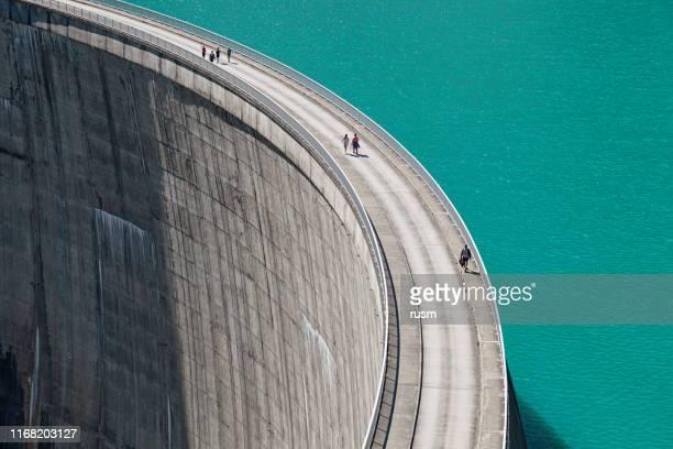 people walking on edge of stausee mooserboden dam, kaprun, austria - panoramica verticale foto e immagini stock