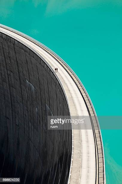 people walking on edge of stausee mooserboden dam, kaprun, austria - hydroelectric power station stock photos and pictures