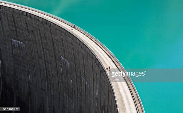 people walking on edge of stausee mooserboden dam, kaprun, austria - tall high stock photos and pictures