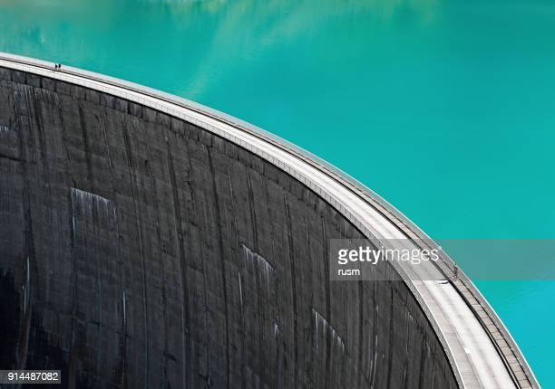 people walking on edge of stausee mooserboden dam, kaprun, austria - reservoir stock pictures, royalty-free photos & images