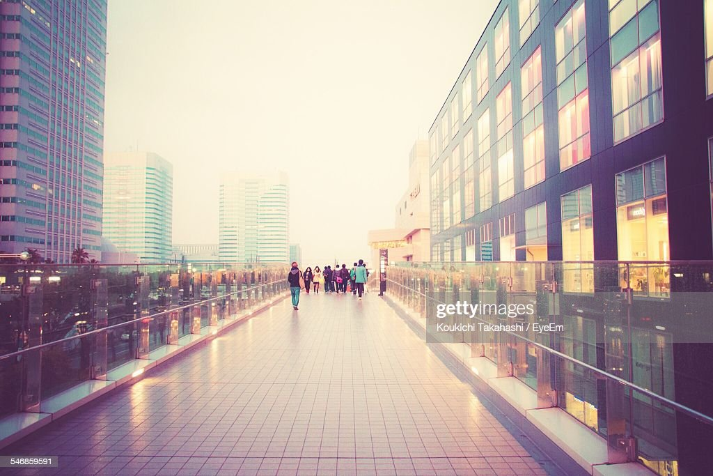 People Walking On Elevated Walkway Amidst City Buildings : Stock Photo