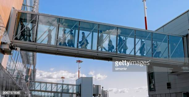 people walking on elevated walkway - passenger boarding bridge stock pictures, royalty-free photos & images
