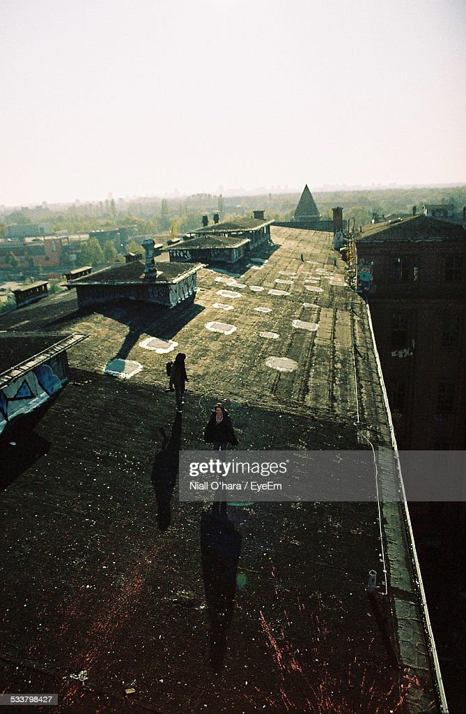 People Walking On Factory Roof Against Clear Sky : Foto stock
