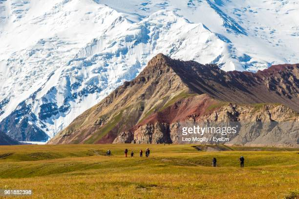 people walking on field against mountains during winter - kyrgyzstan stock pictures, royalty-free photos & images
