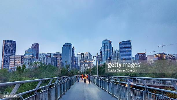 people walking on footbridge against towers in city during sunset - footbridge stock photos and pictures