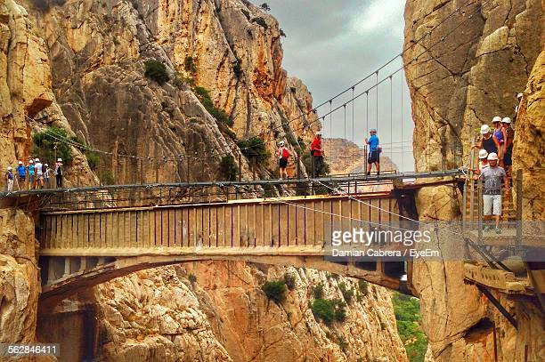 people walking on footbridge amidst rocky mountains - málaga málaga province stock pictures, royalty-free photos & images