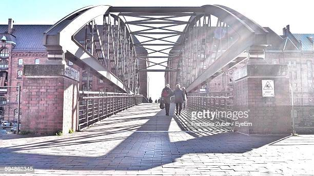 People Walking On Footbridge In City