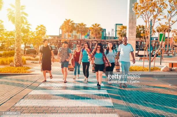people walking on footpath against sky - gulf countries stock pictures, royalty-free photos & images
