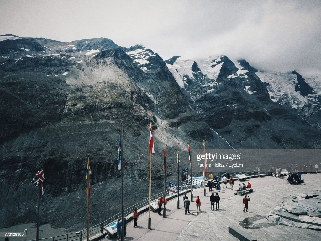 People Walking On Footpath Against Snowcapped Mountain And Sky : Photo