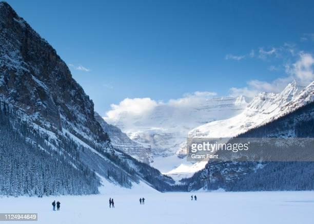 people walking on frozen lake. - lake louise lake stock pictures, royalty-free photos & images