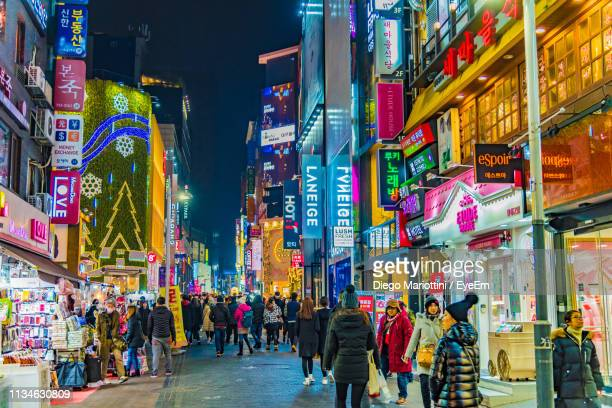 people walking on illuminated street amidst buildings at night - seoul stock pictures, royalty-free photos & images