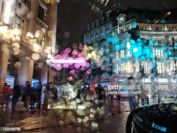 people walking on illuminated street amidst buildings at night - defocussed stock pictures, royalty-free photos & images