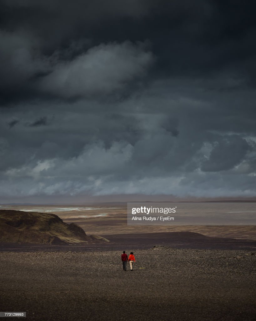 People Walking On Landscape Against Sky : Photo