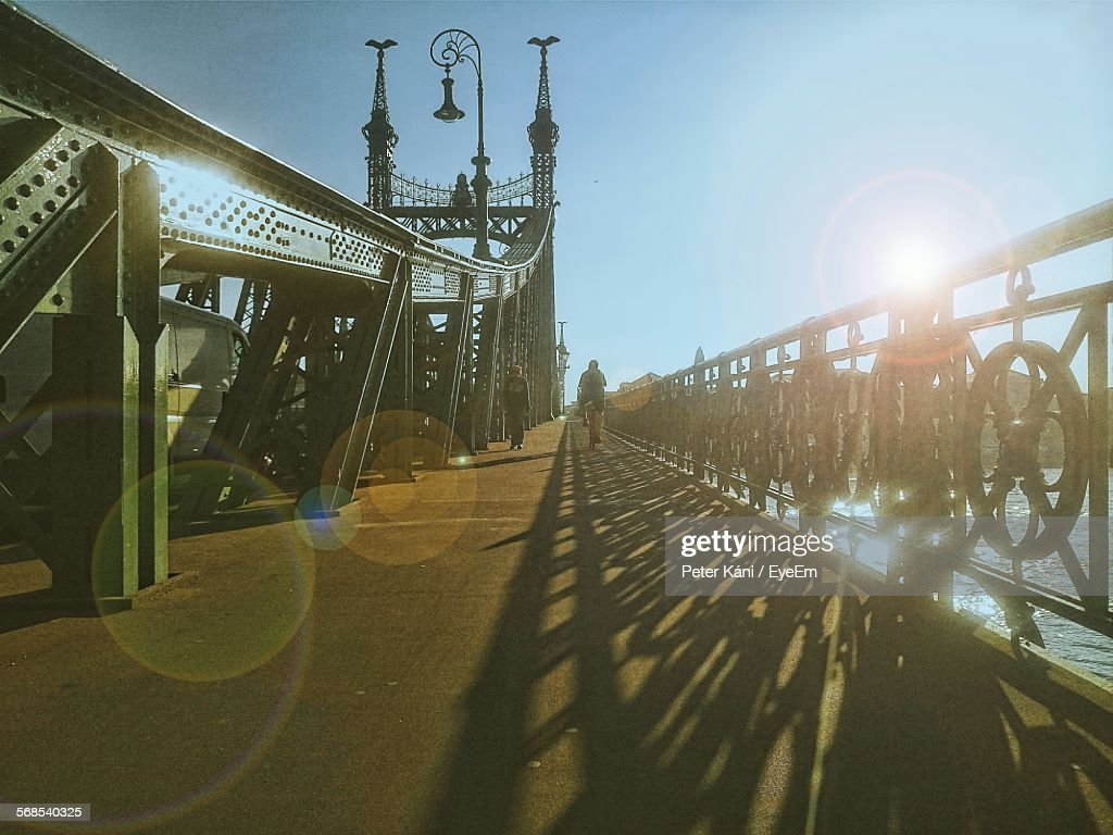 People Walking On Liberty Bridge Over River Danube Against Clear Blue Sky : Stock Photo