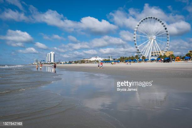people walking on myrtle beach - brycia james stock pictures, royalty-free photos & images