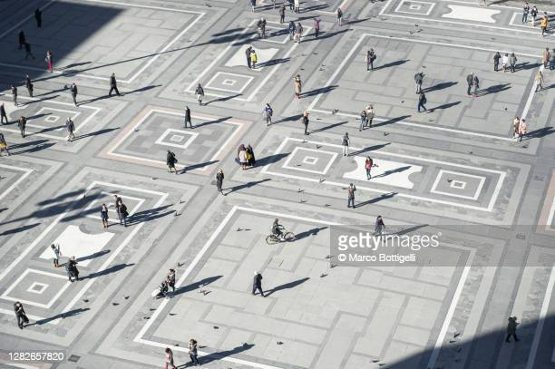 people walking on piazza del duomo, milan, italy - large group of people foto e immagini stock